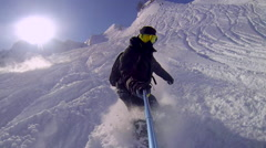 Man riding on snowboard with selfie gopro stick in his hand Stock Footage