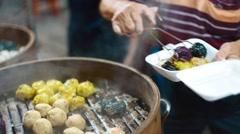 Person serves steaming food on jalan alor food street Stock Footage
