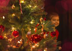 Portrait smiling girl hiding behind Christmas tree Stock Photos