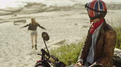 Young man on motorcycle watching woman run onto beach - stock photo