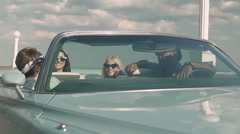 Teenagers having fun sitting in a retro car laughing Stock Footage