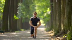 Sportsman stretch in the beautiful park alley. Real time. Super telephoto lens Stock Footage