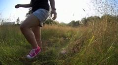 Girl walking through tall green grass in city park, summer sunset Stock Footage
