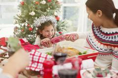 Mother and daughter pulling Christmas cracker at dinner table - stock photo