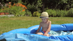 Little boy playing in a pool in the garden Stock Footage