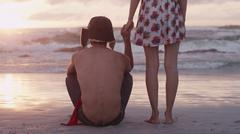Young couple holding hands on beach at sunset Stock Photos