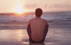 Pensive young man on beach watching sunset over ocean Stock Photos