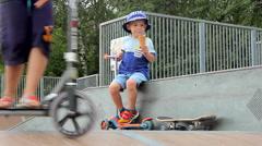 Little boy eating ice-cream on skateboard ramp Stock Footage
