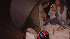 Young couple with flashlight inside camping tent - stock photo