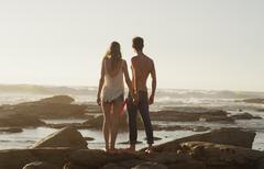 Young couple holding hands and looking at ocean view - stock photo