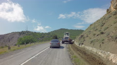 Autotravel Summer south of Crimea. Tractor removes rockfall on the road Stock Footage