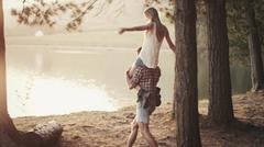 Young man carrying woman on shoulders at lakeside Stock Photos