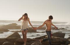 Young couple holding hands and walking on ocean rocks Stock Photos