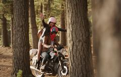 Exuberant young woman riding motorcycle in woods Stock Photos