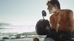 Young man on motorcycle shaving beard near ocean - stock photo