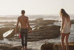 Young couple walking on rocks at ocean Stock Photos