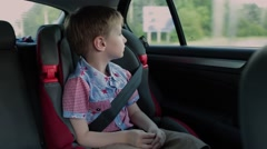 Boy Sitting in the Car Seat During a Trip and Looking Out the Window Stock Footage