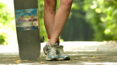4K. Young beautiful legs of  girl   and skate team in summer park Stock Footage