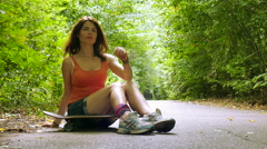 4K. Young beautiful girl sits on  skateboard in park Stock Footage