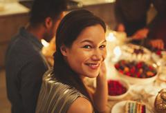 Portrait smiling woman at candlelight dinner party Stock Photos