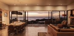 Home showcase interior overlooking ocean at sunset Stock Photos