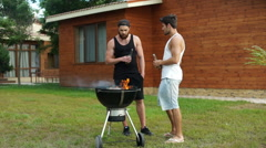 Two men holding a beer bottle while preparing barbecue grill Stock Footage