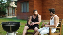 Two men sitting while preparing barbecue grill Stock Footage