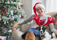 Woman sitting on sofa with dog wearing reindeer antlers near Christmas tree Stock Photos