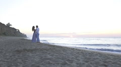 Attractive enloved young couple kissing on the beach at evening. Romantic - stock footage