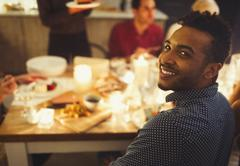 Portrait smiling man enjoying candlelight Christmas dinner Stock Photos