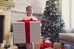 Portrait enthusiastic girl holding large Christmas gift Stock Photos