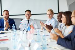 Successful professionals applauding to one of business people after speech Stock Photos