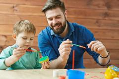 Cute boy and his father creating colorful apple stamps Stock Photos