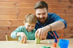 Happy father and son making apple stamps on paper Stock Photos