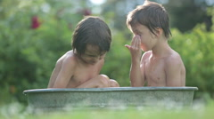 Two children, boy brothers, having a bath outdoors, making soap bubbles, summ Stock Footage
