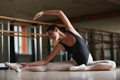 Happy girl stretching her legs during ballet practice Stock Photos