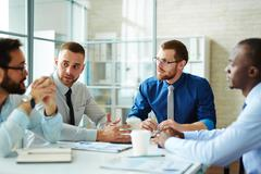 Male employees listening to colleague at briefing Stock Photos