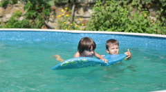 Two boys, swimming in the pool at backyard Stock Footage