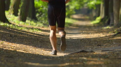 The sportsman run in the beatiful forest. Slow motion. Super telephoto lens shot Stock Footage