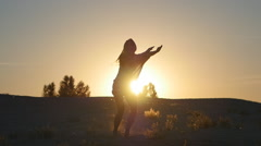 Silhouette of a girl professional dancer jumping at sunset in slow motion Stock Footage