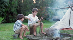 Two sweet children, boy brothers, camping outside summertime on sunset Stock Footage