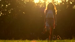 Young woman walking barefoot on the grass holding her high heel shoes in hand Stock Footage