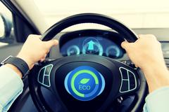 Close up of young man driving car in eco mode Stock Photos
