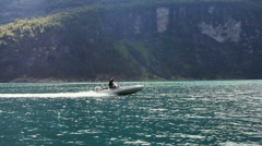 Man on Motor Boat Sailing on River at Sunny Day. Mountains on Background Stock Footage