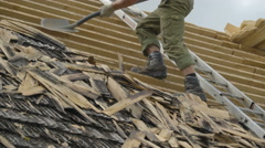 A man removing the wooden shingles - stock footage