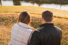 Romantic young couple enjoying autumn nature sitting in a close embrace, view - stock photo