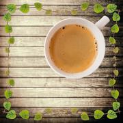 Hot coffee cup with clipping path on rough wood plank and green creeper plant Stock Photos