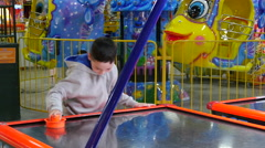 4k, emotional little boy playing in air hockey in entertainment center 1 Stock Footage