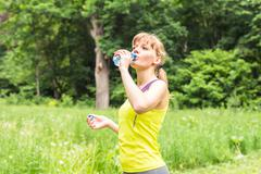 Fitness woman drinking water after work out exercising on summer outdoor Stock Photos