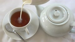 Nice Cup of tea, Pouring Tea from a white teapot and adding Milk into Tea Cup, Stock Footage